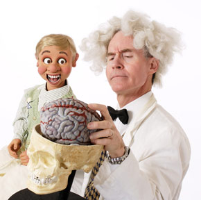Ventriloquist in White Wig holding human skull with brain and Puppet in other hand